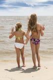 Zwei Mädchen am Strand, der Wasser betrachtet Stockfotografie