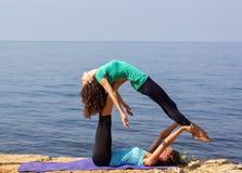 Zwei Mädchen tun acro Yoga Stockbild