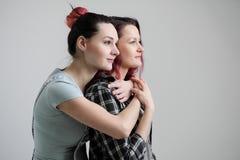 Zwei Mädchen umarmen auf einem weißen Hintergrund Homosexuelle lesbische Paare Zufällige Kleidung stockbilder
