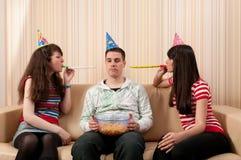 Zwei Mädchen und ein Kerl, der eine Geburtstagsfeier hat Stockfoto