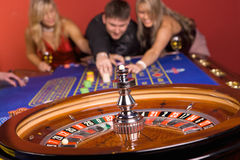 Zwei Mädchen und ein Mann im Kasino lizenzfreie stockfotografie