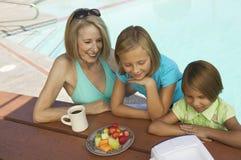 Zwei Mädchen (7-9) und Großmutter, die tragbares durch Swimmingpool fernsieht. Lizenzfreie Stockbilder