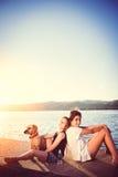 Zwei Mädchen und Hund, die durch das Wasser sitzen Stockfotografie