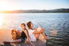 Zwei Mädchen und Hund, die durch das Wasser sitzen Stockfotos