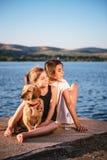 Zwei Mädchen und Hund, die durch das Wasser sitzen Lizenzfreies Stockfoto