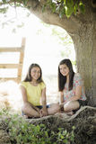 Zwei Mädchen unter einem Baum stockbild