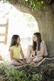 Zwei Mädchen unter einem Baum lizenzfreie stockfotografie