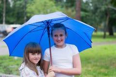 Zwei Mädchen unter einem Regenschirm Stockbilder