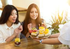 Zwei M?dchen, welche die gesunden und geschmackvollen vegetarischen Kuchen w?hlen lizenzfreies stockbild
