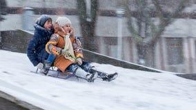 Zwei Mädchen ziehen unten vom Hügel auf einem Schlitten um Winterblizzard, Frost Lizenzfreies Stockfoto
