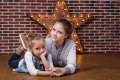 Zwei Mädchen zu Hause in der vorderen Backsteinmauer und im dekorativen Stern Stockfotos