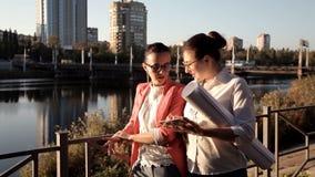 Zwei Mädchenarchitekten stehen den Fluss bereit und besprechen das Bauvorhaben Geschäft, Bau stock video footage
