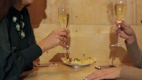 Zwei Mädchengeklirrgläser Champagner stock footage