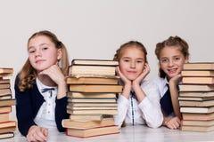 Zwei Mädchenschulmädchen sitzen mit Büchern an seinem Schreibtisch auf der Lektion in der Schule lizenzfreies stockfoto