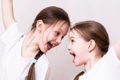 Zwei Mädchenschwestern lächeln emotional an einander lizenzfreie stockfotos
