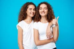Zwei Mädchenzwillinge, die, Blinzeln, stellend wie blauer übermäßighintergrund lächeln dar Lizenzfreie Stockfotos