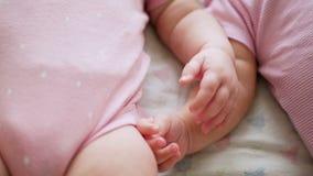 Zwei Mädchenzwillings-Griffhände beim Lügen stock video