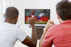 Zwei Männer in überwachendem Fernsehen des Wohnzimmers Lizenzfreie Stockfotografie