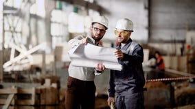 Zwei Männer auf Standort Projektplan besprechend Seitenansicht von Arbeitskräften in den Schutzhelmen, die auf Bauplan auf Hinter stock video