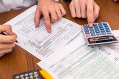 Zwei Männer berechnet Einkommenssteuerform Lizenzfreie Stockfotografie