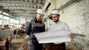 Zwei Männer in den Schutzhelmen arbeiten im Baubereich mit den Arbeitskräften zusammen, die im Hintergrund schweißen vorarbeiter stock video