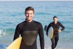 Zwei Männer in den Wetsuits mit einem Surfbrett an einem sonnigen Tag Stockfotografie