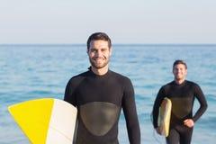 Zwei Männer in den Wetsuits mit einem Surfbrett an einem sonnigen Tag Stockbild