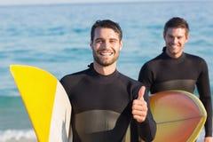 Zwei Männer in den Wetsuits mit einem Surfbrett an einem sonnigen Tag Stockfoto