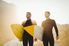 Zwei Männer in den Wetsuits mit einem Surfbrett an einem sonnigen Tag Stockfotos