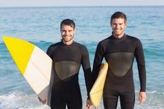 Zwei Männer in den Wetsuits mit einem Surfbrett an einem sonnigen Tag Stockbilder