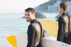 Zwei Männer in den Wetsuits mit einem Surfbrett an einem sonnigen Tag Lizenzfreies Stockbild