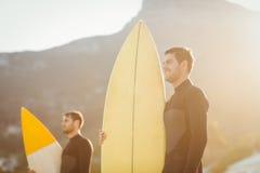 Zwei Männer in den Wetsuits mit einem Surfbrett an einem sonnigen Tag Lizenzfreie Stockfotografie