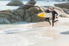 Zwei Männer in den Wetsuits mit einem Surfbrett an einem sonnigen Tag Lizenzfreie Stockfotos