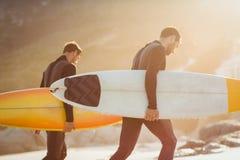 Zwei Männer in den Wetsuits mit einem Surfbrett an einem sonnigen Tag Lizenzfreie Stockbilder