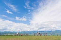 Zwei Männer, die auf der Bank gegen den Hintergrund der Berge und des perfekten Himmels sitzen stockbild
