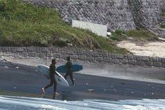 Zwei Männer, die auf einen schwarzen Strand surfen gehen lizenzfreie stockfotos