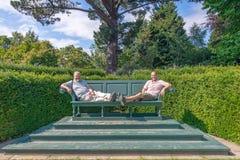 Zwei Männer, die auf einer riesigen Bank, Bodnant-Garten, Wales sitzen lizenzfreie stockfotografie