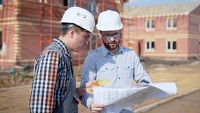 Zwei Männer, die auf neuem Projekt des Baus auf Standort coworking sind stock video footage