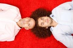 Zwei Männer, die auf rotem Teppich liegen Stockbild