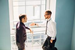 Zwei Männer, die in der Lobby des Büros sprechen Stockbild