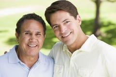 Zwei Männer, die draußen lächelnd stehen Stockfotografie