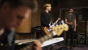 Zwei Männer, die E-Gitarren spielen und ein singender Sänger stock video