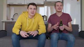 Zwei Männer, die ein Fußballspiel und eine Flasche Bier öffnen aufpassen stock footage