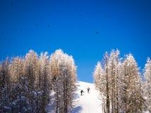 Zwei Männer, die einen Schnee klettern, bedeckten Hügel Lizenzfreies Stockbild