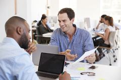 Zwei Männer, die Geschäftsunterlagen in einem beschäftigten Büro besprechen stockfotos