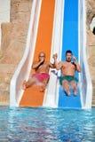 Zwei Männer, die hinunter die Diafreunde eines Wassers genießen einen Wasserschlauch reiten, reiten Lizenzfreie Stockfotos