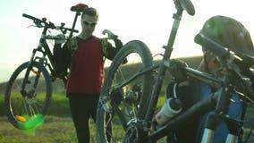 Zwei Männer, die ihre Fahrräder tragen stock video