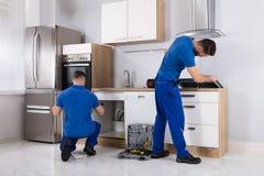 Zwei Männer, die Induktions-Ofen und Abflussrohr überprüfen lizenzfreie stockfotos
