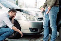 Zwei Männer, die nach einem Autounfall auf der Straße argumentieren lizenzfreie stockfotos