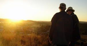 Zwei Männer, die Sonnenuntergang überwachen Lizenzfreie Stockfotos